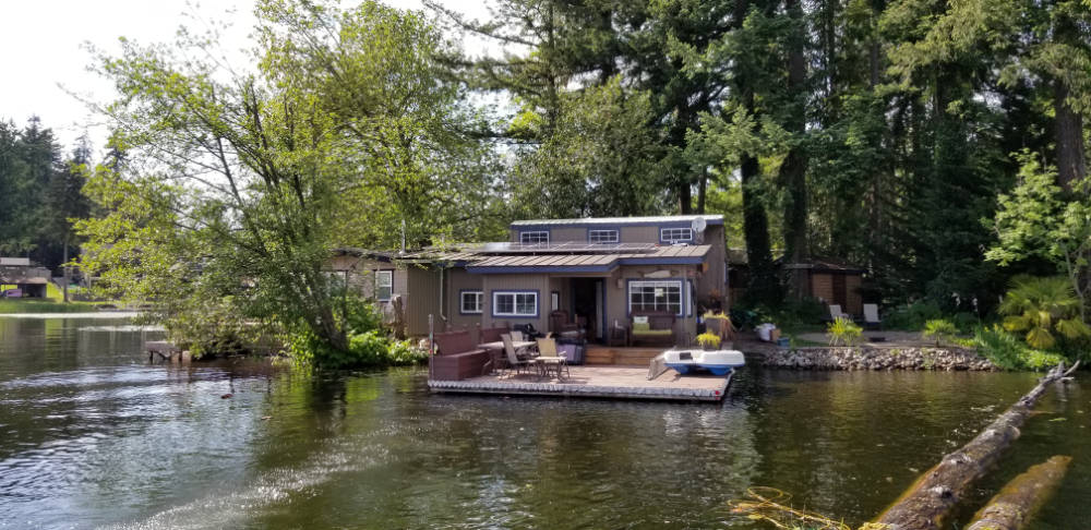 Home on lake with solar panels on roof.